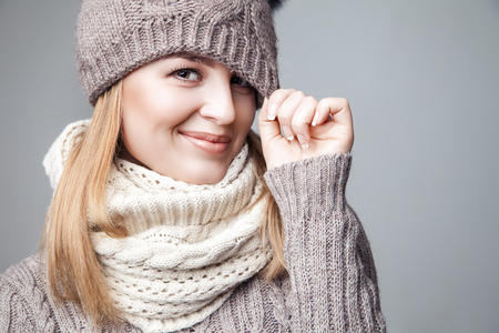 Beautiful blond young girl wears winter scarf and hat over gray background