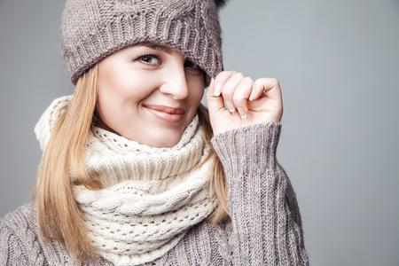 Bella bionda ragazza indossa inverno sciarpa e cappello su sfondo grigio Archivio Fotografico - 49556589