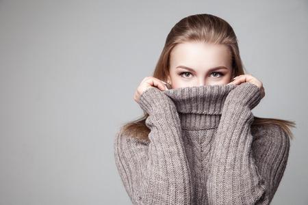 sueter: Hermosa joven rubia lleva suéter de invierno sobre fondo gris
