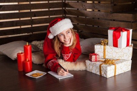 female christmas: Happy young girl with Christmas presents laying on wooden floor whiting letter to Santa Stock Photo