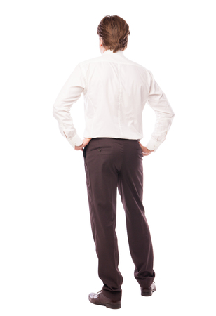 in vouge: businessman standing back with arms at hips over white background