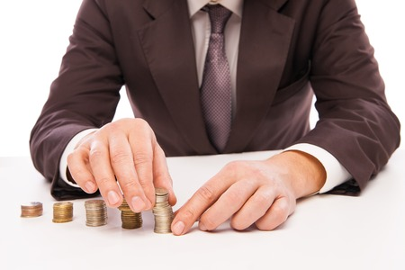 by placing: Close-up Of Businessman Placing Coin Over Stack Of Coins At Desk over white backround