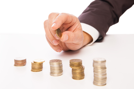 Close-up Of Businessman Placing Coin Over Stack Of Coins At Desk over white backround