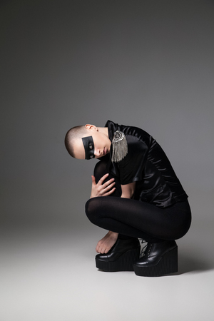 vouge: agressive beautiful bald sitting woman  with mask makeup posing on background