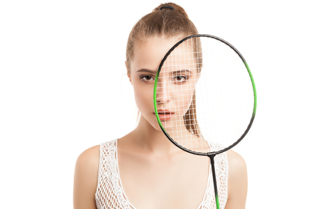 badminton: closeup of beautiful young girl holding badminton racket over white background