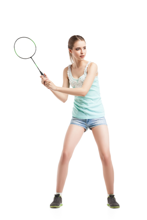 racket sport: beautiful young girl playing with badminton racket in sneakers over white background Stock Photo