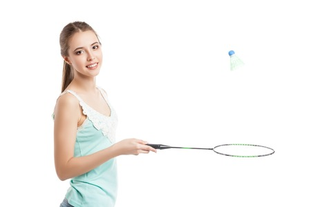 badminton: beautiful young girl playing with badminton racket in sneakers over white background Stock Photo