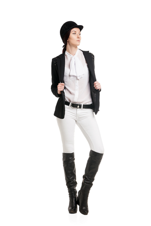 Young woman in riding clothes over white background Stock Photo