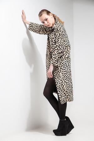 femme brune sexy: belle jeune fille en manteau imprim� l�opard sur fond blanc