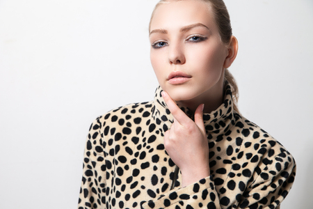 sexy young woman: Closeup of beautiful young Girl in leopard print coat over white background