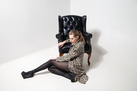 sexy young girl: Красивая молодая девушка в леопардовым принтом пальто рядом кожаной черной кресло на белом фоне