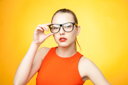 cynical: Strict young woman in large glasses over bright orange background