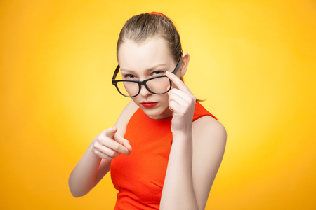strict: Strict young woman in large glasses pointing by finger over bright orange background
