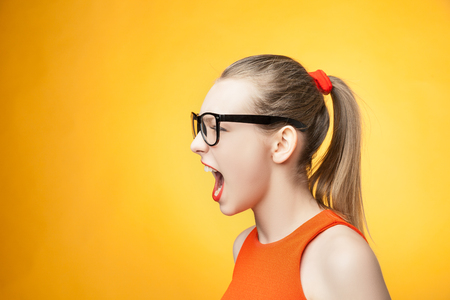 strict: Strict young woman in large glasses screaming over bright orange background