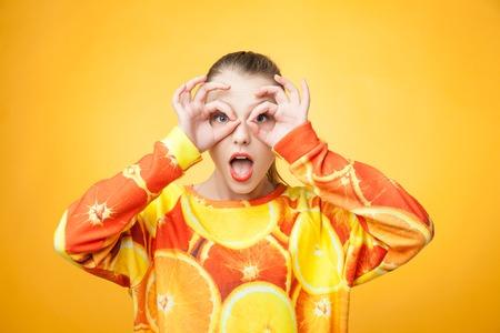 swagger: Portrait of young pretty funny smiling girl wearing orange printed sweatshirt