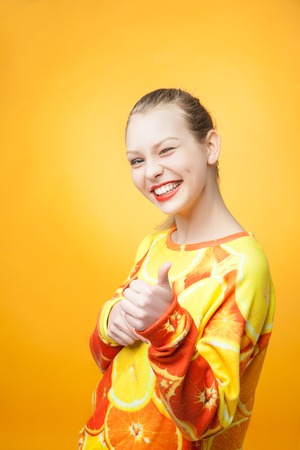 clothes interesting: Portrait of young pretty funny smiling girl wearing orange printed sweatshirt