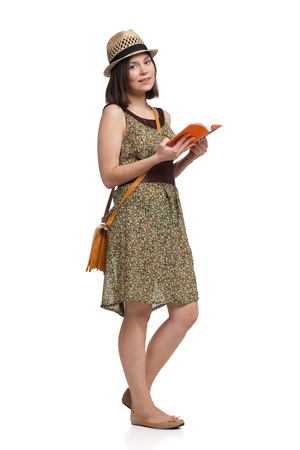 guidebook: young pretty girl in summer dress and hat holding guidebook over white backgroud