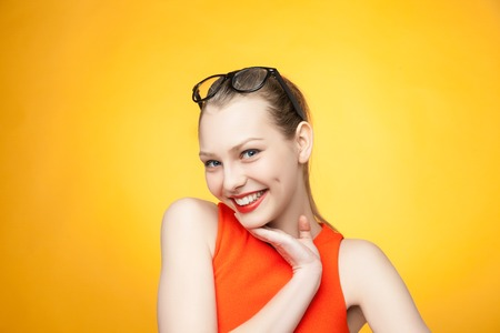 Portrait of an attractive fashionable young  woman in orange dress on yellow background