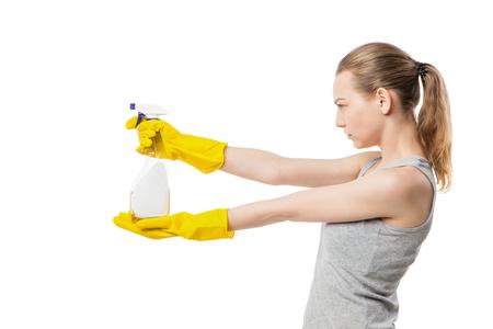 aseo: Perfil de la mujer joven con spray de limpieza de ventanas, concentrado, ama de casa, aislado en blanco