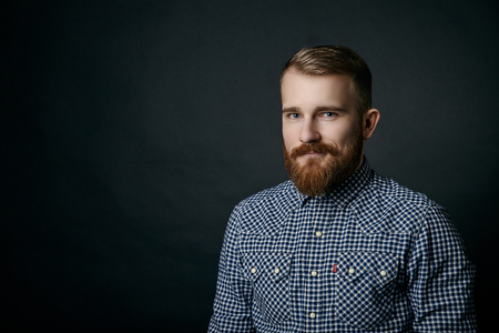 Smiling red bearded handsome stylish man in blue checkered shirt studio portrait on dark background