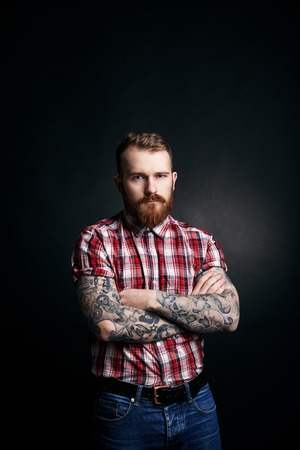 folding arms: Red bearded handsome stylish man with tattoes in red checkered shirt and jeans, folding arms, studio portrait on dark background
