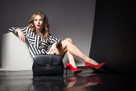 Portrait of elegant beautiful blonde woman with red lips sitting near black fashion bag