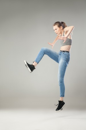 mid air: Young blonde woman jumping in mid air while looking away.Studio shot Stock Photo