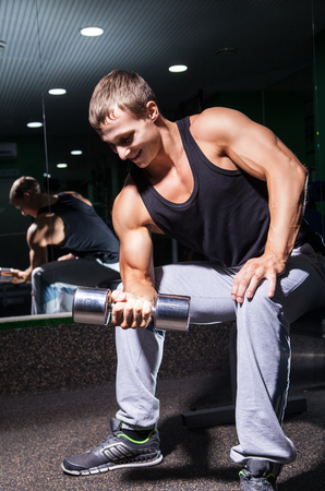 Portrait of smiling muscular man doing concentration curls with dumbbell on bench Stock Photo