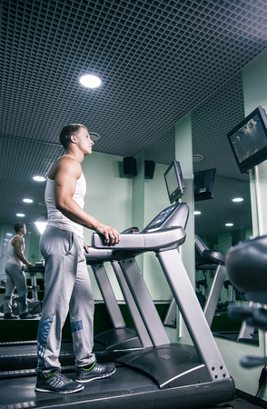masculinity: Young muscular man on track in gym watching TV Stock Photo