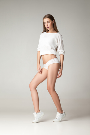undies: Portrait of young brunette in shirt,undies and sneakers posing against of white background Stock Photo