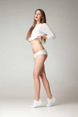 undies: Young brunette putting off shirt while wearing undies and sneakers.Studio shot