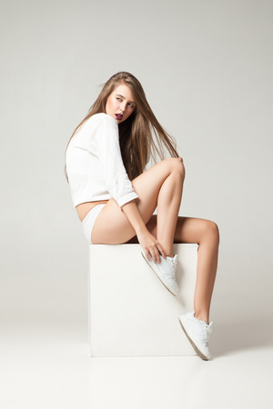 undies: Portrait of young brunette looking away while posing on white cube in undies.Studio shot