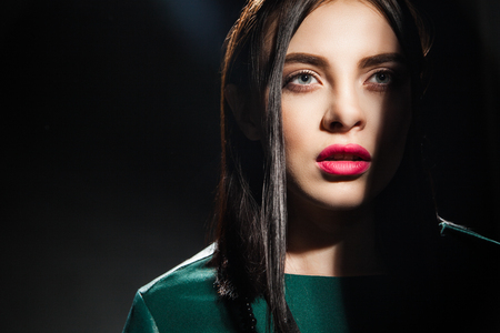 half face: Beautiful model with bright lips and half face covered with shadow Stock Photo