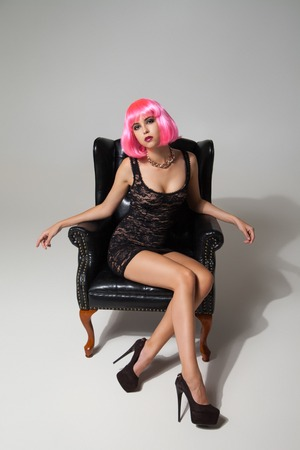 pink posing: Portrait of model in pink wig and lace black dress posing on leather chair.Studio shot