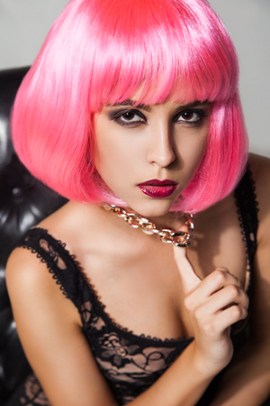 golde: Portrait of young model in pink wig holding golde chain necklace while looking at camera