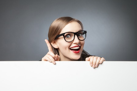 Portrait of beautiful young woman in glasses with index finger up above blank space