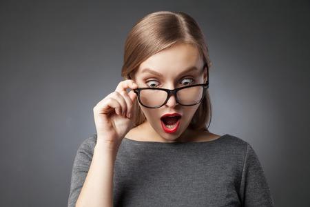Überraschte Frau mit den roten Lippen in den Gläsern schaut mit offenem Mund