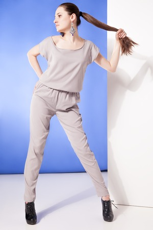blue overall: Beautiful model posing in overall against of blue background.