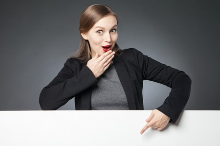 dedo indice: Wide-eyed woman with red lips in jacket showing blank space with index finger