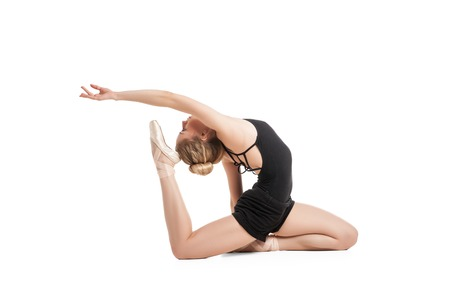 to bend: Side view of female ballet dancer bending in black.Isolated