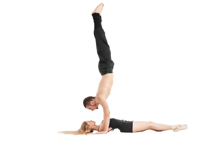 handstand: Gymnast in handstand above woman lying on floor.Isolated