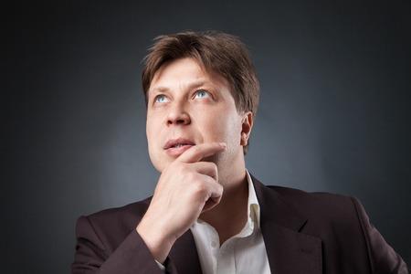 puzzlement: portrait of pensive adult man looking up.studio shot