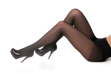 Unrecognizable woman in black tights and high heels lying on floor.White background.Isolated