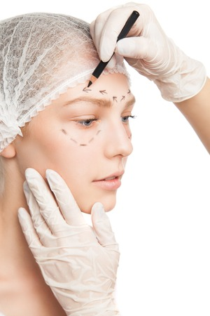 surgeons hat: Close-up of plastic surgeon in gloves drawing contour on patients face Stock Photo