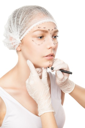 surgeons hat: Close-up of unrecognizable plastic surgeon drawing marks on womans face.Studio shot Stock Photo