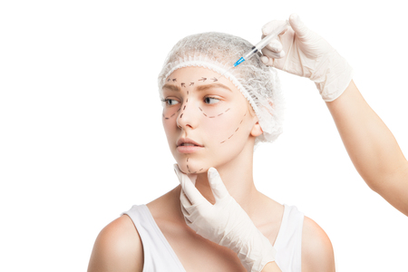 injected: Portrait of young woman in medical hat being injected with syringe in face.Studio shot
