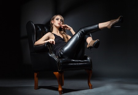 legs up: Beautiful young model with legs up posing on leather chair Stock Photo