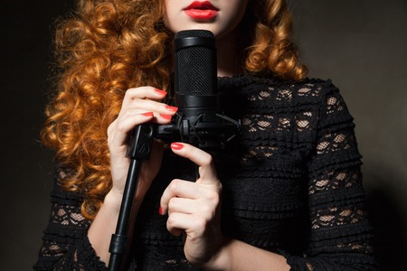incognito: Close-up of unrecognizable red-haired woman singing in black mic