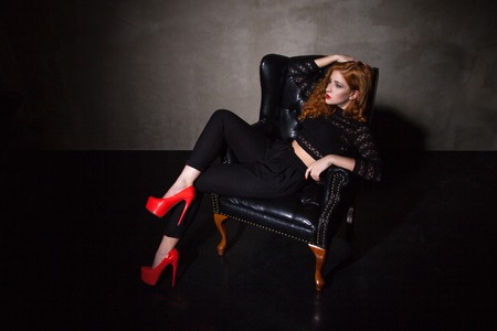 Red-haired model posing on black leather chair in red high heels Stock Photo