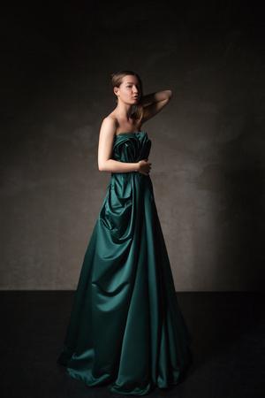 arm raised: Model in beautiful long dress with arm raised looking down.Studio shot